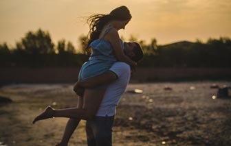 A photo of a man happily carrying a woman in his arms at the beach